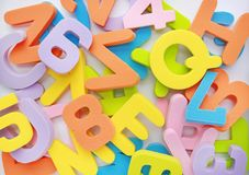 Background messy heap of sponge rubber alphabet letters and numbers. Royalty Free Stock Photos