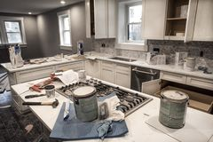 Messy home kitchen during remodeling fixer upper with kitchen cabinet doors. Open cluttered with paint cans and tools, granite counter tops, appliances royalty free stock photo