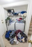 Messy Laundry Room with Piles of Clothes Vertical View royalty free stock photo