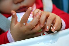 Messy Little Hands. Baby's discover of rice sticking to her hands royalty free stock photos