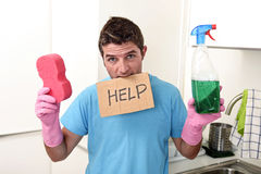 Messy man in stress in washing gloves holding sponge and detergent spray bottle asking for help Stock Photo