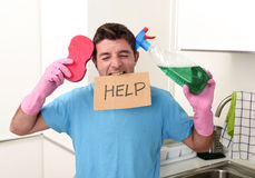 Messy man in stress in washing gloves holding sponge and detergent spray bottle asking for help Stock Image