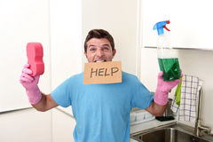 Messy man in stress in washing gloves holding sponge and detergent spray bottle asking for help. Young messy man in stress in washing rubber gloves holding royalty free stock photos