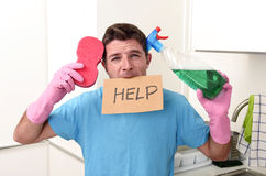Messy man in stress in washing gloves holding sponge and detergent spray bottle asking for help Stock Images