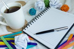 Messy Morning Work Planning. A mug of coffee, note pad and pen on top of white cloth Stock Photo