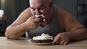 Messy obese man greedily eating cake with whipped cream, addiction to sweets Royalty Free Stock Photography
