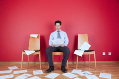 Messy office. Businessman reading a document in a messy office full of papers on the floor Royalty Free Stock Photo