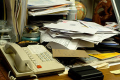 Messy Office Desk. A Clustered Office Desk with phone and files Stock Photo