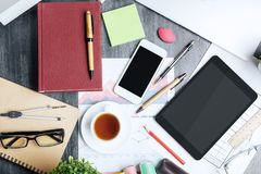 Messy office desktop. Top view of messy desktop with various, supplies, devices and sketches. Close up Royalty Free Stock Photo