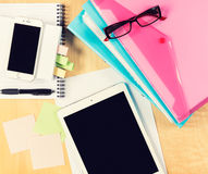 Messy office table with digital tablet, smartphone, reading glasses, notepad and filling folders. View from above Royalty Free Stock Photo