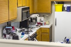 Messy Old Kitchen. With oak cabinets, tile countertops, gas stove, green flooring and piles of dishes stock image