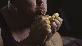 Messy overweight man stuffing with greasy hamburger, psychology of overeating
