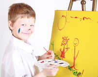 Messy painter. Kindergarten child painting a picture with lots of colors Royalty Free Stock Images