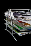 Messy paper tray with papers. Paper tray overflowing with papers,mail and other documents. Isolated on black background stock photography