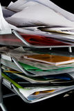 Messy paper tray with papers. Paper tray overflowing with papers,mail and other documents. Isolated on black background royalty free stock image