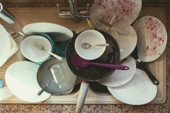 Stained Dirty Dishes In Kitchen Sink. A Messy Pile of Dirty Dishes And Utensils In Kitchen Sink stock photos