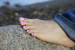 Messy pink pedicure foot with jeans Royalty Free Stock Photos
