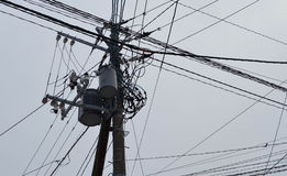 Messy power line cable and transformer - cloudy and snow day Royalty Free Stock Photos