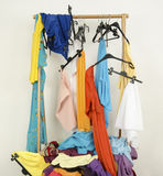 Messy rack of clothes and hangers. Royalty Free Stock Images