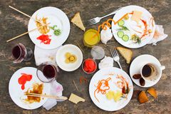 Messy table after party. Leftover food, spilled drinks, dirty dishes Royalty Free Stock Photo