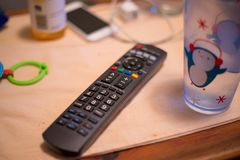 Messy table top with remote control, water glass, phone, can, charger, and children`s toy stock photos