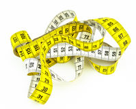 Messy tape measure. A yellow and white tape measure in a messy position, on a white surface Stock Photos