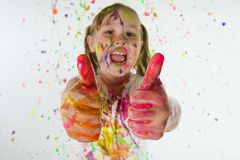 Messy Thumbs Up. A 6 year old girl covered in colorful paint and giving two thumbs up Stock Images