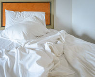 Messy unmade bed with pillow Stock Photography