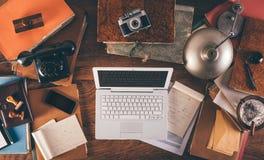 Messy vintage desktop with laptop Royalty Free Stock Image
