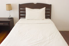 Messy white bed and one pillow. Light white wall in morning Stock Photo