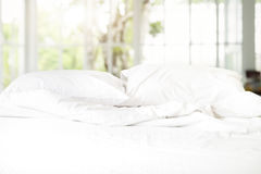 Messy white bed with pillow and blanket on concrete wall backgro Royalty Free Stock Photo
