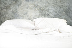 Messy white bed with pillow and blanket on concrete wall backgro Stock Image