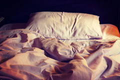Messy white bed and pillow in the morning. Vintage or retro color toned Stock Photos