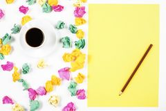 Messy white workplace with supplies. Top view and close up of messy white office workplace with various colorful supplies and coffee cup Royalty Free Stock Photo