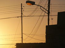Messy wires in urban landscape. Sunset over messy electrical cables in urban landscape Royalty Free Stock Image