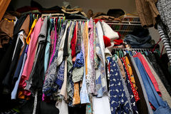 Messy Women's Closet Filled with Colorful Clothes. A messy young women's closet is fill with many outfits of colorful clothing, shirts, and dresses royalty free stock images