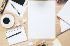 Messy workplace with blank papersheet Royalty Free Stock Images