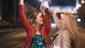 Mest bra flickvänner har gyckel tillsammans i nattstaden som rymmer i deras händer mousserande fyrverkerier i ultrarapid arkivfilmer