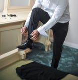 Mest bra man som får klar för en special dag En brudgum som sätter på skor, som han får iklädda formella kläder dräkt för brudgum Royaltyfri Bild