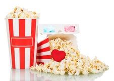 Mest full popcornask med ett genomsnitt av spridda mellanmål, hjärtor och exponeringsglas som 3d isoleras på vit Royaltyfri Fotografi