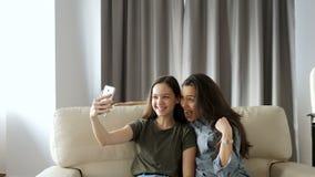 Mest ung och äldre syster som tar en selfie på soffan lager videofilmer