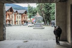 Courtyard of the tourist town of Mestia in the Svaneti region with a cow in the arch and a sculpture of Swan on a horse in the bac stock photo