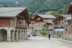Streets of the tourist town of Mestia of the Svaneti region with classic houses surrounded by the Caucasus Mountains stock image