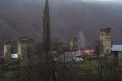 Mestia på dimmig dag med gamla försvartorn fotografering för bildbyråer