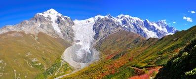 Mestia-Ushguli trek, Svaneti Georgia. A panoramic view of glacier Adishi and colorful red trees in the trek from Mestia to Ushguli, Svaneti region, Georgia Stock Photo