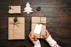 Mestiere e contenitori di regalo attuali fatti a mano del Natale sul fondo di legno della tavola Immagine Stock