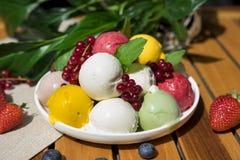 Mestoli crema del gelato alla frutta sopraelevati sul piatto bianco con i pezzi di frutti e di bacche, serviti con parecchi cucch fotografia stock