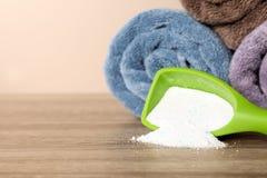 Mestolo con il detersivo ed asciugamani puliti sulla tavola contro il fondo di colore, spazio per testo fotografia stock