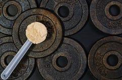 Mestolo del proteina del siero su fondo nero Vista superiore Fotografia Stock