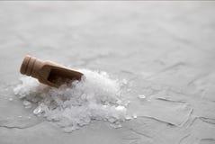 Mestolo di legno attaccato in un mucchio dei cristalli bianchi di sale marino su un fondo concreto La pala di legno attacca fuori fotografie stock libere da diritti